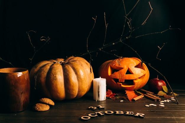 Деревянные надписи «31 октября» лежат перед крупными разорванными тыквами на хэллоуине Бесплатные Фотографии