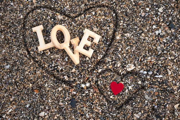 Wooden letters forming the word love with a red heart on beach sand, inside a heart made with the fingers. concept of san valentine Premium Photo