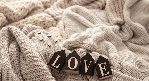 Деревянные буквы составляют слово «любовь» на фоне уютных вязаных вещей. Бесплатные Фотографии