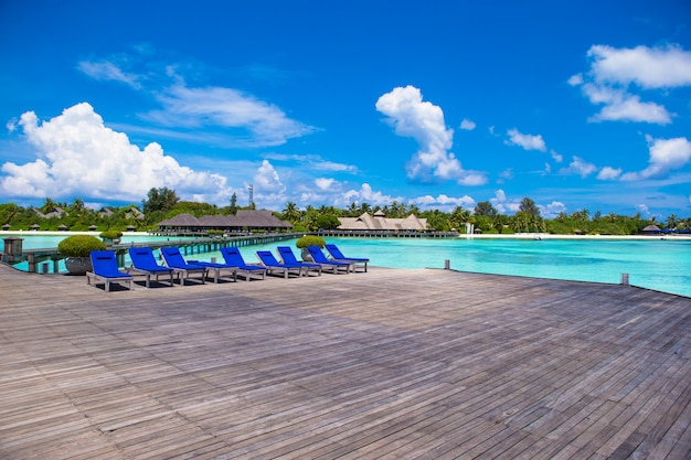 Outdoor Natural Gas Fire Pit Table, Wooden Lounge Chairs On On A Wooden Pier At Maldives Premium Photo