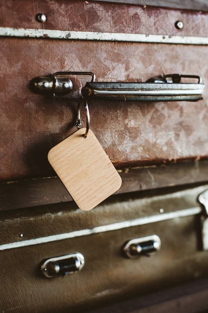 Wooden luggage tag on the handle of an old suitcase. close up. Premium Photo