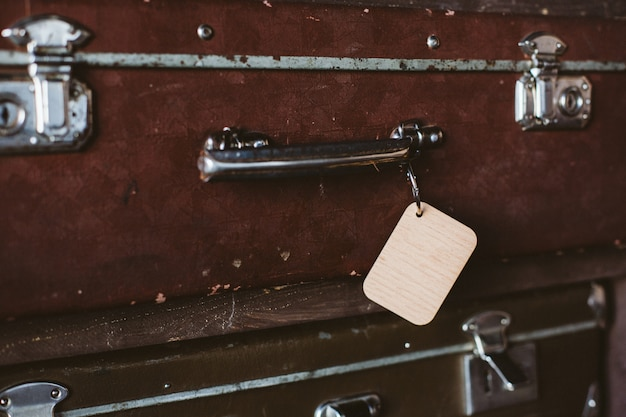Wooden luggage tag on the handle of an old suitcase. mock up Premium Photo