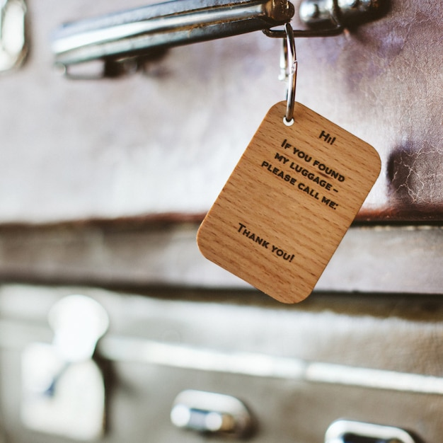 Wooden luggage tag with the inscription on the handle of a vintage suitcase. Premium Photo