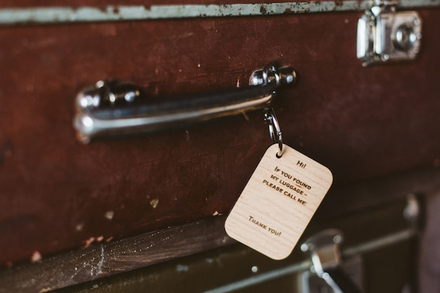 Wooden luggage tag with the inscription on the handle of a vintage suitcase Premium Photo