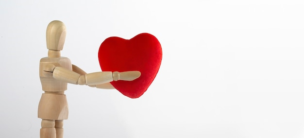 흰색에 그의 손에 심장 입상을 들고 나무 남자 프리미엄 사진