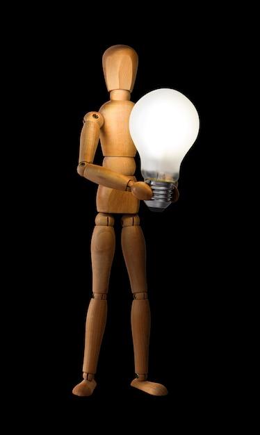Wooden mannequin holding light bulb Premium Photo