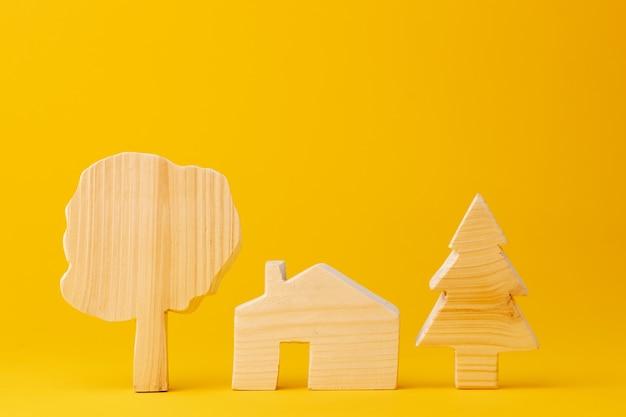 黄色の背景に木製のミニ家モデルをクローズアップ Premium写真