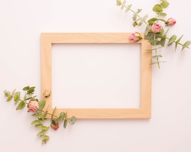 Wooden picture frame decorated with pink roses and eucalyptus Free Photo
