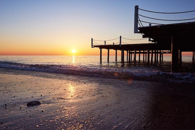 派手なオレンジ色の夕日に木製の桟橋。 無料写真