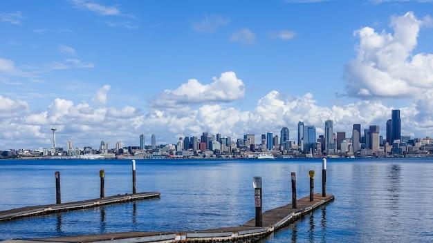 美しい雲の下で米国シアトルの街と海の上の木製の桟橋 無料写真