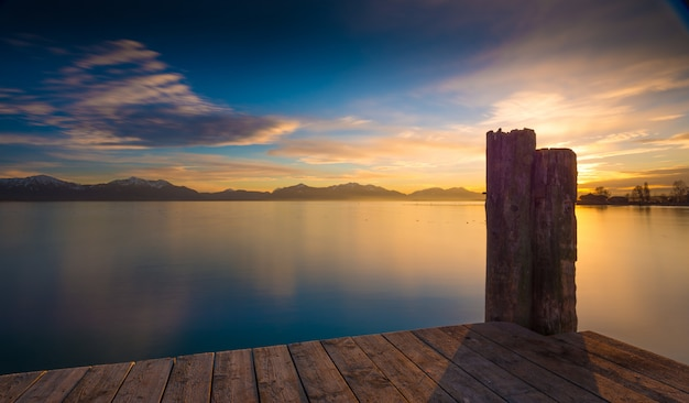 山脈と日の出のある穏やかな海の上の木製の桟橋 無料写真