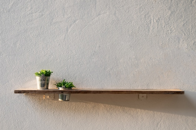 Wooden plank on wall with vase plant Premium Photo