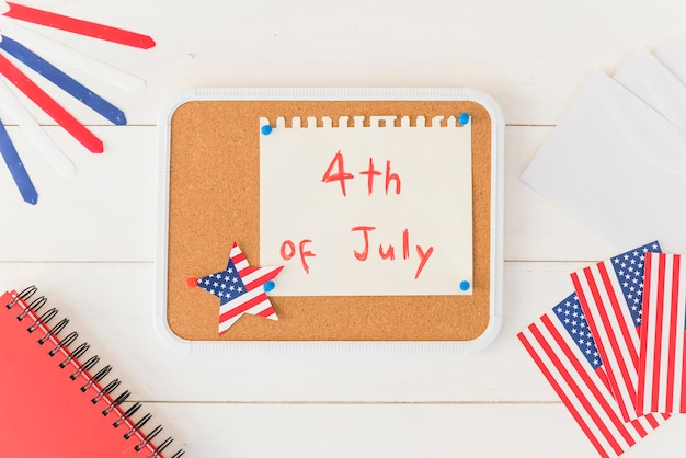 Wooden plank with paper with text 4th of july Free Photo