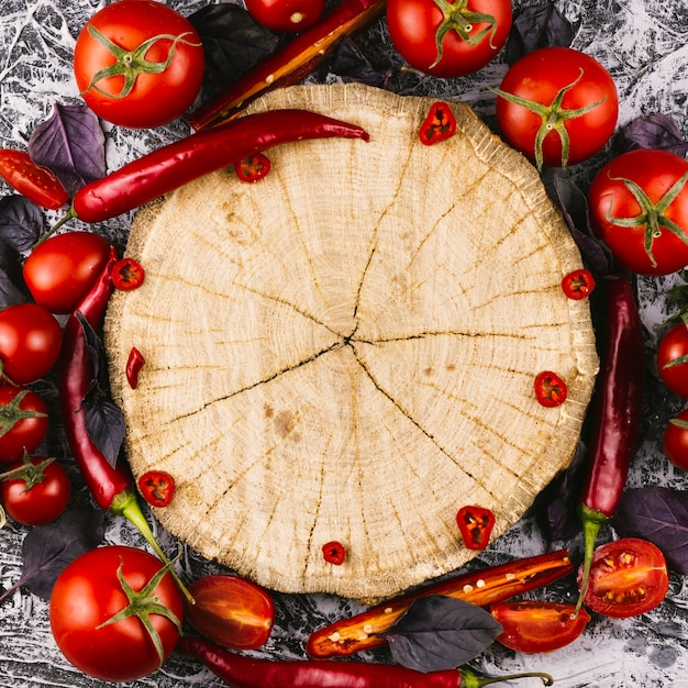 Wooden plate surrounded by chilli peppers and tomatoes Premium Photo