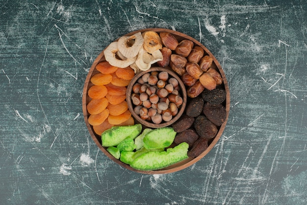 Wooden plate with dried fruits on marble table Free Photo