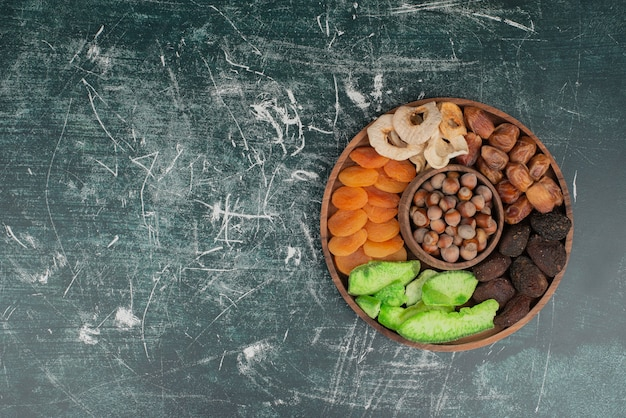 Wooden plate with dried fruits on marble wall Free Photo