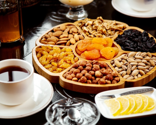 Wooden plate with dried fruits and nuts Free Photo