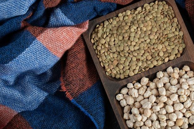 黒に生のエンドウ豆とレンズ豆が入った木の板。 無料写真