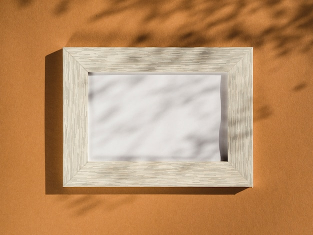 Wooden portrait frame on a beige background covered with leaf shadows Free Photo