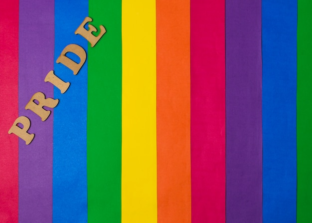 Wooden pride word and bright gay flag Free Photo