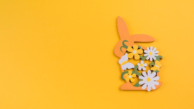 Wooden rabbit with flowers on yellow table Free Photo