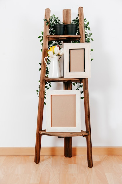 Wooden rack with frames and flowers Free Photo