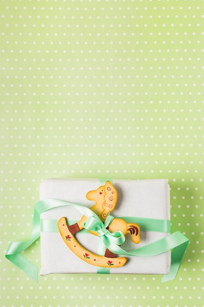 Wooden rocking horse tied on present box with green ribbon