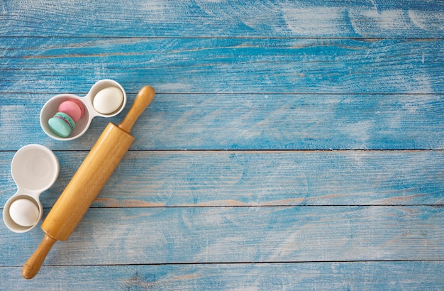 Wooden rolling pin on blue wooden table. Premium Photo