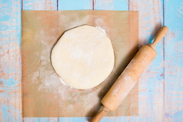 Wooden rolling pin over the flat dough over the parchment paper on wooden table Free Photo