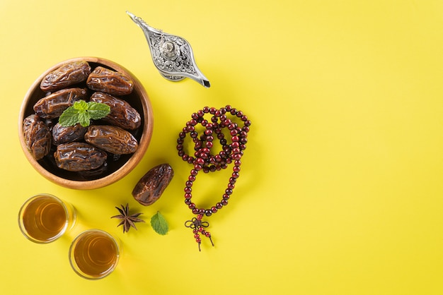 Wooden rosary and date fruit for ramadan wall Premium Photo