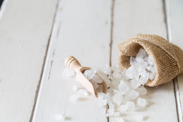 Wooden scoop of crystalline sugar and sugar bag on white wooden floor Premium Photo