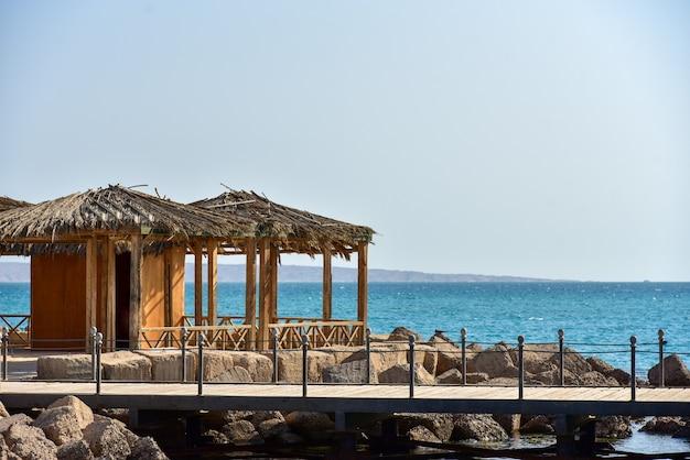 海と山々を背景にした木製の桟橋。 Premium写真