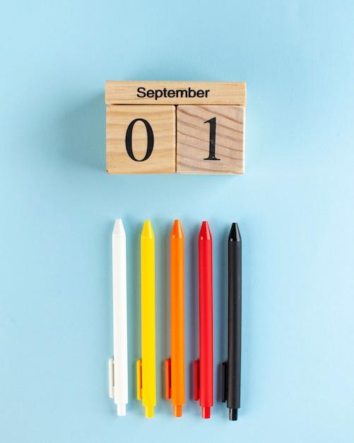 1 сентября деревянный календарь, цветные ручки на синей поверхности. арт-концепция начала учебного года. Premium Фотографии