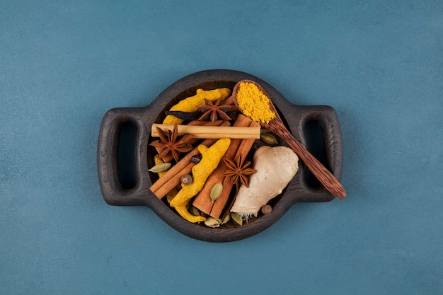 Wooden serving plate with set of spicy spices for making indian masala tea (masala chai), golden milk and other drinks. Premium Photo