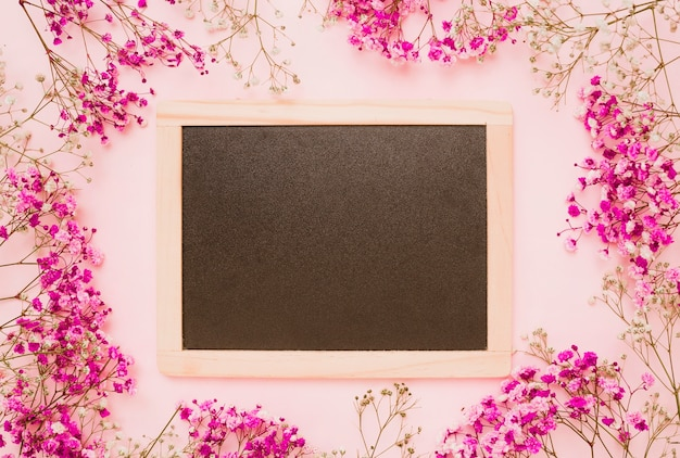 Wooden slate decorated with baby's-breath flowers on pink background Free Photo