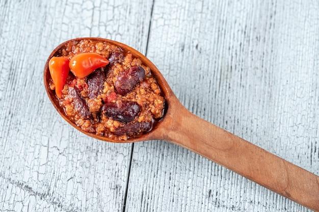 Wooden spoon of chili con carne close up Premium Photo