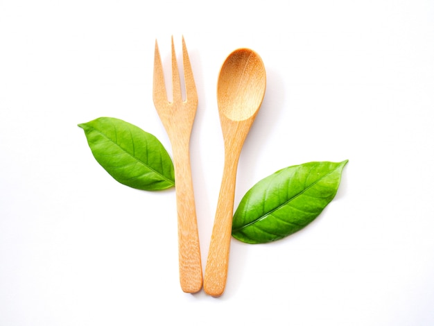 Wooden spoon and fork and green leaf, natural wooden utensils eco-friendly and safe for health. Premium Photo