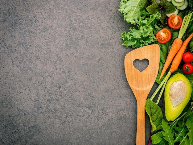 Wooden spoon and vegetables on dark stone background. Premium Photo