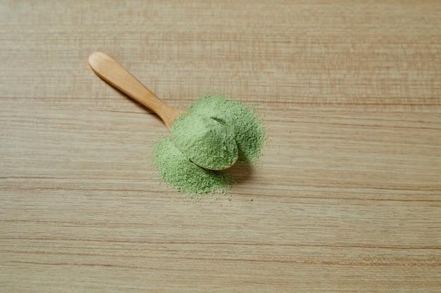 Wooden spoon with powdered matcha green tea Premium Photo
