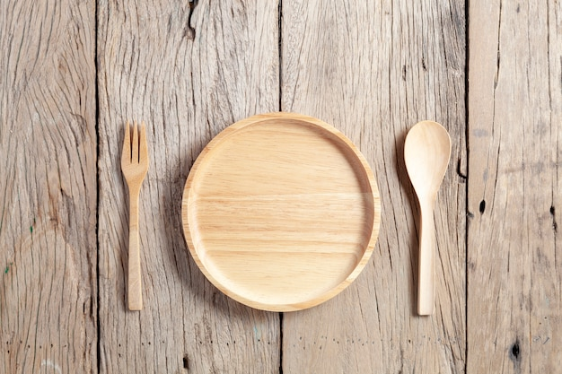Wooden spoon and wooden plate on old wood table background Premium Photo
