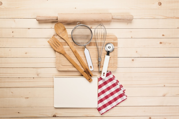 Wooden spoons and other cooking tools with red napkins on the kitchen table. Premium Photo
