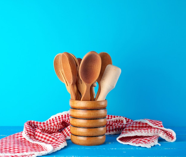 Wooden spoons in a wooden container on a blue table Premium Photo