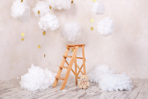 Wooden staircase stool with clouds in the children room. scandinavian style. rustic room interior. christmas holiday decorations. Premium Photo