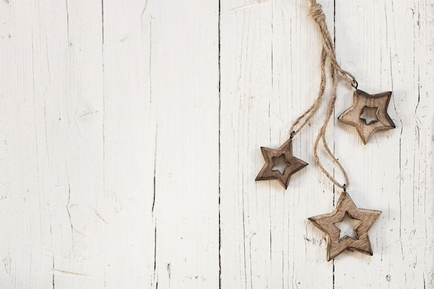 Wooden stars for christmas tree over white wooden background Free Photo
