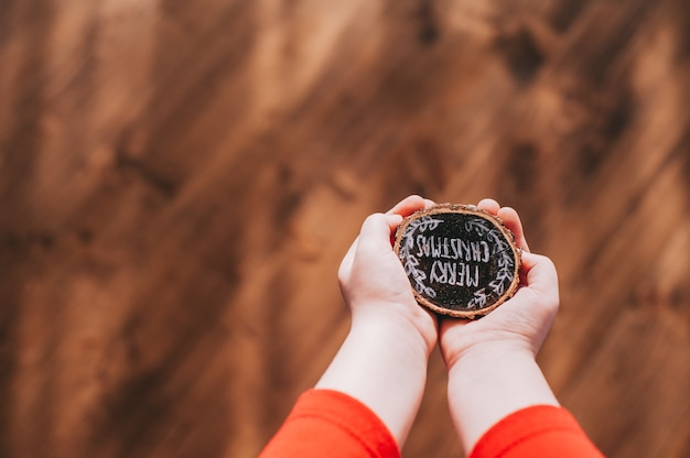 Wooden stump in children's hands with the words, merry christmas Premium Photo