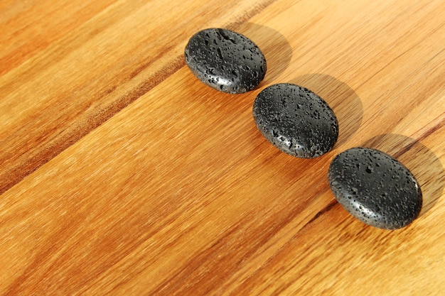 Wooden surface with black lava beads in a spa salon - great for background or wallpaper Free Photo