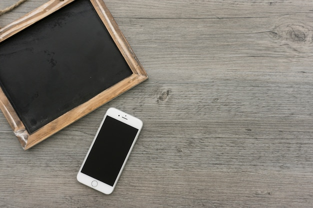 Wooden surface with cell phone and blank slate Free Photo