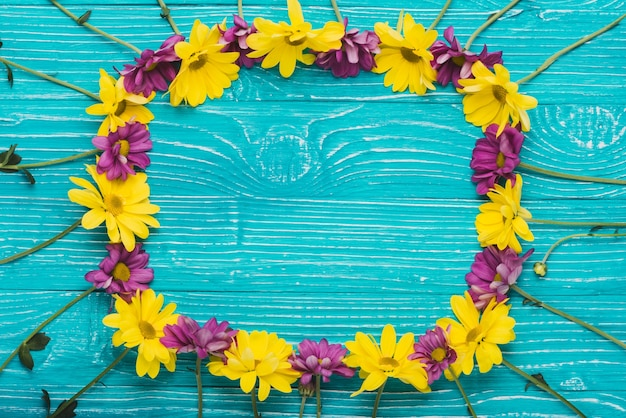 Wooden surface with flowers forming a frame Free Photo