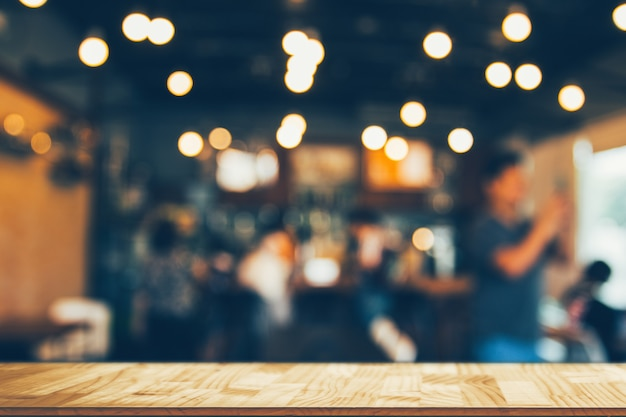 Wooden table in front of abstract blurred coffee shop lights backgroundâ Premium Photo