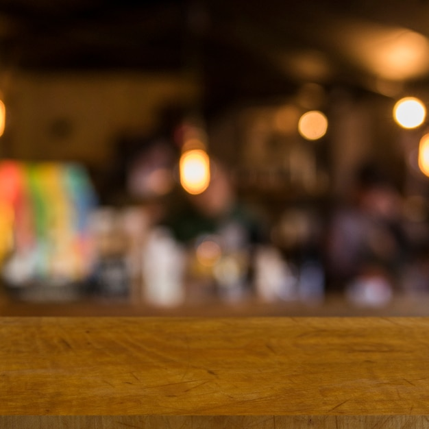 Wooden table in front of blurred restaurant lights Free Photo